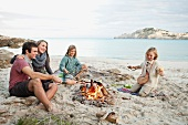 Friends cooking sausages over a campfire on the beach