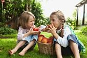 Zwei Mädchen essen Äpfel im Garten