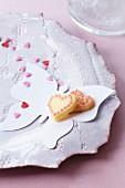 Herzplätzchen mit Zuckerherzen auf Papierschmetterling