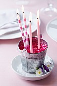 Candles and pink decorative pebbles in little metal bucket decorating table