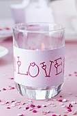 Drinking glass used as lantern and decorated with 'Love' written on paper