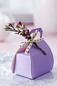 Lilac gift box shaped like a handbag and decorated with flowers