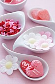 Sugar hearts and flowers made from edible paper in bowls