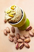 Pistachios in an eggcup with roasted pistachios to one side