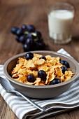 Cornflakes mit Roten Weintrauben und Milchglas im Hintergrund