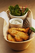 Breaded chicken schnitzel with a dip and salad