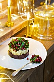 Individual prune layer cake topped with parsley and pomegranate salad