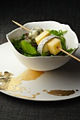 A cheese skewer on a bowl of salad leaves