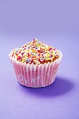 A cupcake decorated with colourful sugar sprinkles