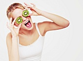 A woman holding kiwi slices in front of her eyes