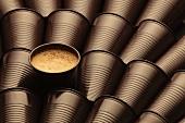 Kaffee im Becher zwischen leeren Plastikbechern