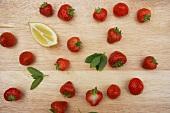 Frische Erdbeeren, Minzeblättchen und Zitronenschnitz auf Holzbrett