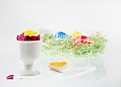 A boiled egg with the top cut off, in an eggcup, with an Easter nest of colourful eggs in the background