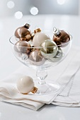 White, gold and silver Christmas tree baubles in a glass dish