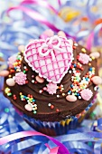 A chocolate cupcake topped with a pink heart for a party