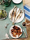A picnic of barbecued fish, chicken and asparagus, on the beach