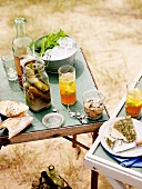 A picnic on the beach with iced tea, pickled mussels, pickled gherkins and goat's cheese