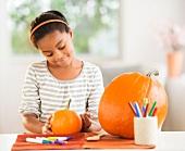 A girl decorating a Halloween pumpkin