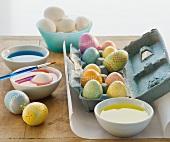 Verzierte Eier neben Schalen mit Ostereierfarbe
