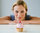 Woman looking at cupcake