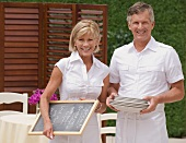 Couple preparing outdoor restaurant for service