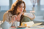 Woman reading letter and stirring tea