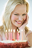 A woman looking at a birthday cake