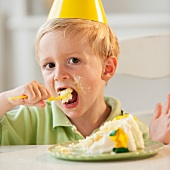 Young child eating birthday cake