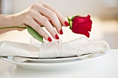 Hand putting a red rose on a place setting
