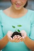 Girl (12-13) holding seedling