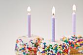 Brennende Geburtstagskerzen auf bunten Cupcakes