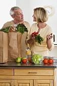 Älteres Pärchen vor Einkaufstüten mit frischen Lebensmitteln