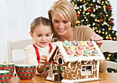 Mother and daughter making gingerbread house