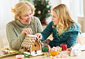 Grandmother with granddaughter (8--9) making gingerbread house