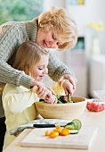 Grandmother and granddaughter (8-9) preparing salad together