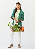 Studio shot of woman holding shopping basket with vegetables