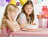 Young sisters with birthday cake at table