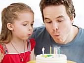 Vater und Tochter blasen die Geburtstagskerzen aus
