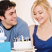Man watching girlfriend smile at birthday cake
