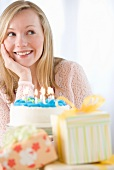Woman with birthday cake and gifts