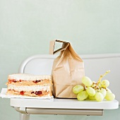 Sandwich and grapes next to paper bag