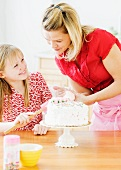 Mother and daughter decorating birthday cake