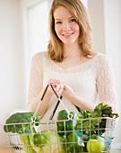 Woman holding basket of green vegetables
