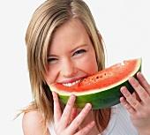Junge Frau beisst genussvoll in ein Stück Wassermelone
