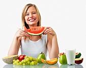 Junge Frau mit verschiedenen Früchten vor sich und einem angebissenen Stück Wassermelone in der Hand