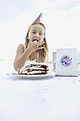 Young girl eating birthday cake