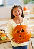 Portrait of girl (10-11) holding Jack o lantern