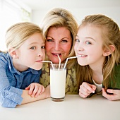 USA, Jersey City, New Jersey, mother and daughters (8-11) drinking milk through straws