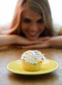 Frau betrachtet einen Cupcake