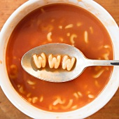 Close up of soup with letter noodles on spoon forming www site